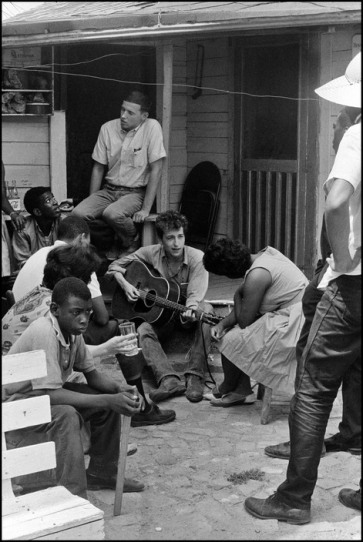 USA. Greenwood, Mississippi. 1962 After giving a concert in a cotton field with Pete Seeger and Theo Bikel, Bob Dylan plays behind the SNCC office. Bernice Reaon, one of the original Freedom Singers and later the leader of Sweet Honey in the Rock, listens. Mendy Samstein sits behind Dylan and talks to Willie Blue.